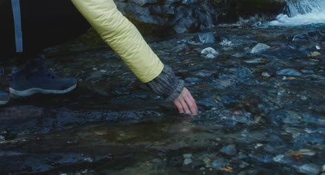 Hiker-Touching-Mountain-River-CU