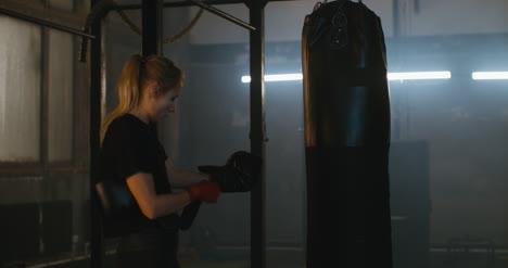 Mujer-poniéndose-guantes-de-boxeo