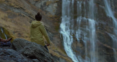 Woman-Walking-Towards-Waterfall