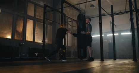 Woman-and-Trainer-Boxing-Punching-Bag