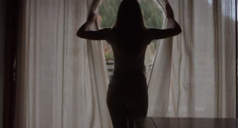 Mujer-abriendo-cortinas-en-Montaña-Lodge