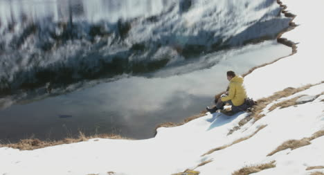 Excursionista-sentado-junto-al-lago-congelado