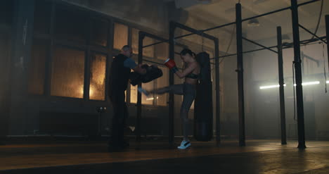 Kickboxing-de-mujer-con-entrenador-en-el-gimnasio