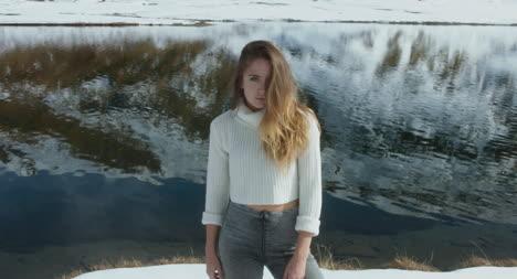 Mujer-junto-a-un-lago-nevado