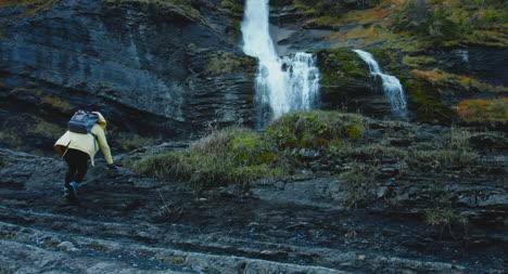 Girl-Hiking-Up-Towards-Waterfall