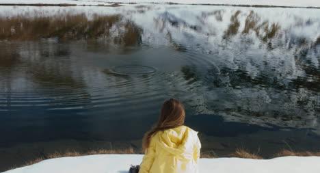 Wanderer-Wirft-Schneeball-In-Den-See-02