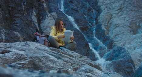 Hiker-Reading-Map-by-Waterfall-01