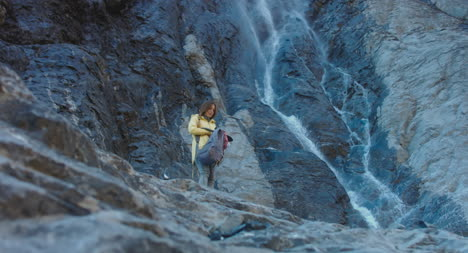Hiker-Opens-Backpack-by-Waterfall