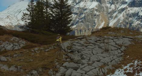 Hiker-Climbing-Rocky-Hillside