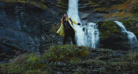 Woman-Dancing-In-Front-of-Waterfall