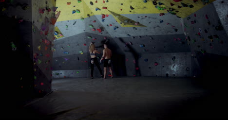 Man-Helping-Woman-on-Climbing-Wall
