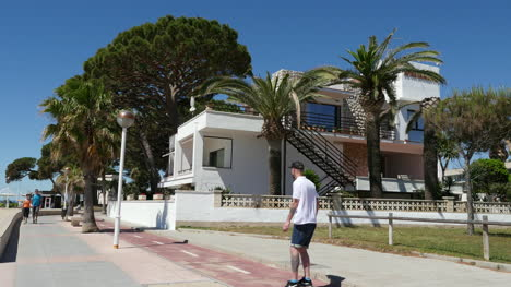 Spain-Cambrils-Skateboarder-And-Monocycle-By-Apartments