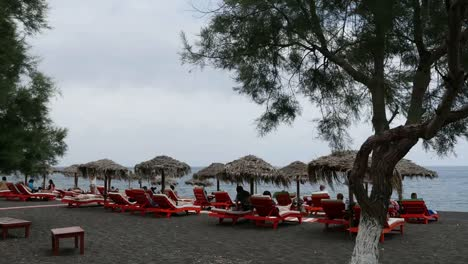 Greece-Santorini-Perissa-Tourists-Relaxing-On-Black-Sand-Beach