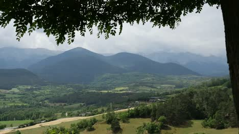 Spain-Pyrenees-Leaves-Frame-A-View-Of-Distant-Mountains