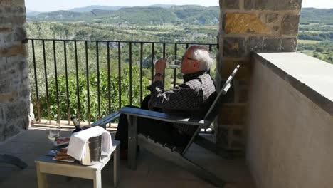 Spain-A-Man-Drinks-Wine-On-A-Balcony-In-The-Spanish-Pyrenees