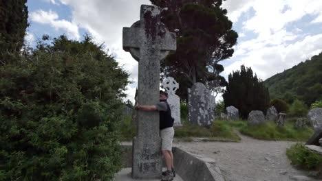 Irland-Glendalough-Keltischer-Klostermann-Umarmt-Hochkreuz