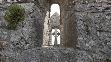 Ireland-Clonmacnoise-A-Celtic-Cross-Is-Seen-Through-A-Stone-Opening
