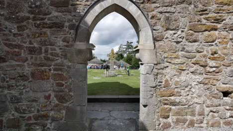 Ireland-Clonmacnoise-A-High-Cross-And-Tourists-Through-A-Window