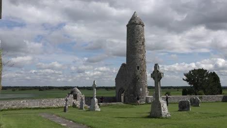 Irland-Clonmacnoise-Ein-Runder-Turm-Steht-Inmitten-Keltischer-Kreuze-Am-Shannon-Fluss