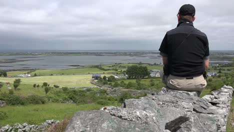 Ireland-County-Clare-Man-On-Wall-Looks-At-Landscape-