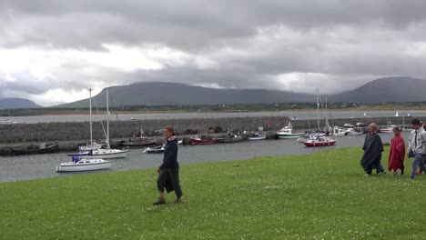 Ireland-Mullaghmore-People-In-Rain-Gear-Pass-A-Boat-Harbor