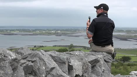 Ireland-Man-On-Stone-Wall-Photographs-With-Phone-Pan