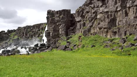 Iceland-Pingvellir-Man-Standing-By-Waterfall