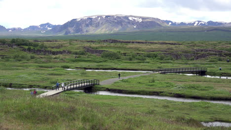 Iceland-Pingvellir-People-Cross-Bridge-Over-Stream