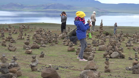 Iceland-Landscape-With-Cairns-And-Woman-Taking-Photos-Pan
