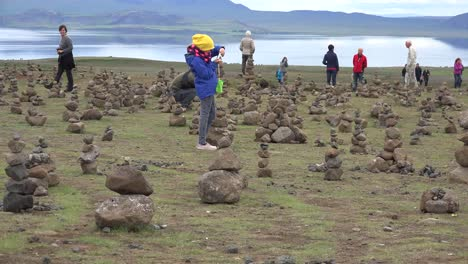 Iceland-Landscape-With-Cairns-And-Woman-Taking-Photos