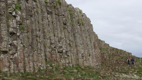Northern-Ireland-Giants-Causeway-Tourists-On-Rocks-Below-Columns-