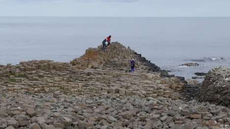 Northern-Ireland-Giants-Causeway-With-Couple-Climbing-For-Picture-