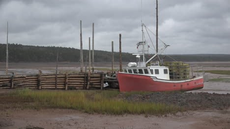 Canada-Nova-Scotia-Red-Boat-By-Log-Dock-Under-Clouds