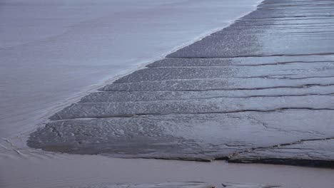 Water-Moves-Along-The-Edge-Of-A-Mud-Flat