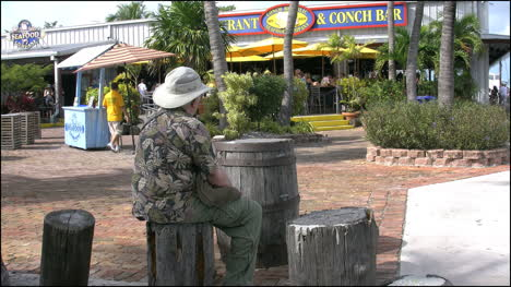 Florida-Key-West-Harbor-Area-Man-Sitting-On-Log