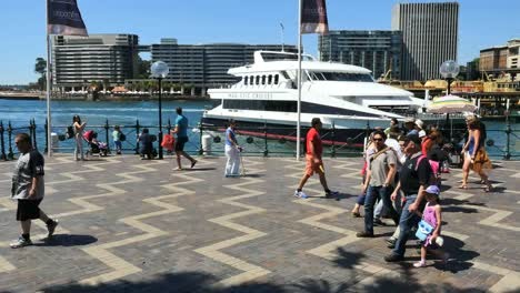 Australia-Sydney-People-Walking-By-Water-As-An-Excursion-Boat-Pulls-Out