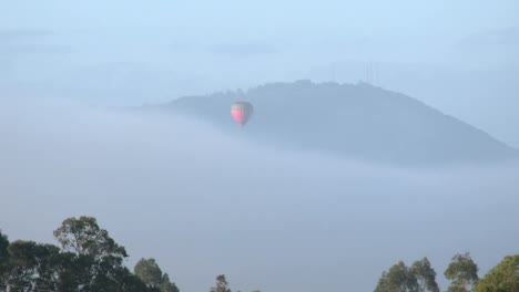 Australia-Outlook-Hill-With-Balloon-Descending-Toward-Mist-Zoom-In