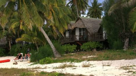 Aitutaki-Lodge-With-People-On-Beach