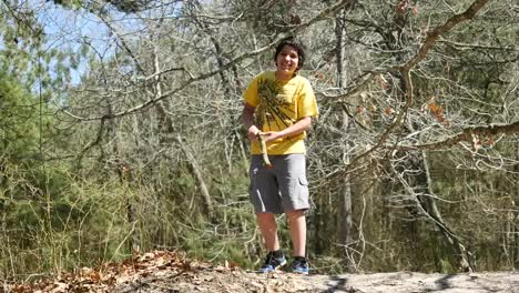 Virginia-Boy-Plays-With-Stick-In-Woods
