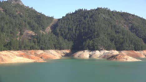 California-Shasta-Lake-With-Low-Water-Level-And-Forest-Above