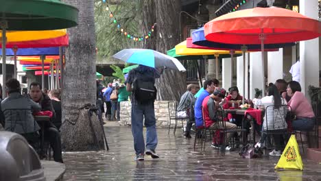 Texas-San-Antonio-Man-With-Umbrella-Walks-Through-Cafe