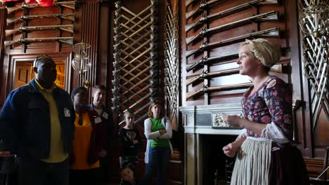 Virginia-Colonial-Williamsburg-Woman-Lectures-With-Guns-On-Wall