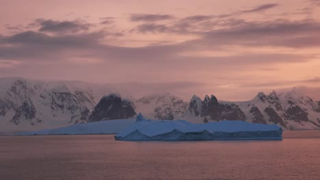 Antarctica-Sailing-By-Iceberg-In-Evening-Zoom-In