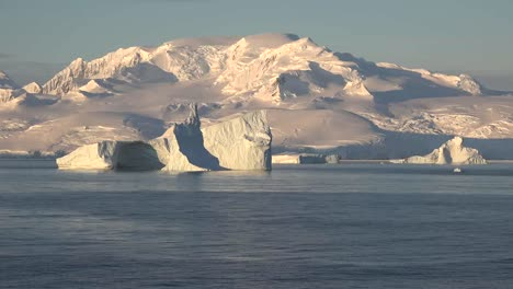 Antarctica-A-Large-Iceberg-Floats-Past-A-Snowy-Mountain