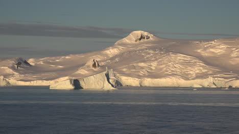 Antarctica-An-Iceberg-And-A-Snowy-Mountain-In-Golden-Light