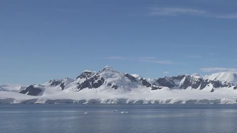 Antarctica-Distant-Mountains-In-Sun-Pans-And-Zooms-Out