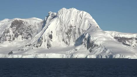 Antarctica-Snowy-Cliffs-Rise-Above-Water-Zoom-In