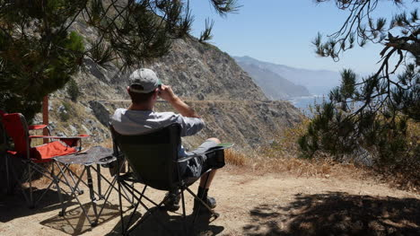 California-Big-Sur-Man-In-Chair-With-Binoculars