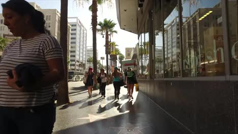 California-A-Backlit-View-Of-People-Walking-Down-A-Hollywood-Sidewalk