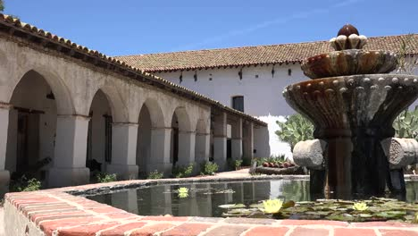 California-Mission-San-Miguel-Arcangel-Colonnade-And-Church-From-Fountain